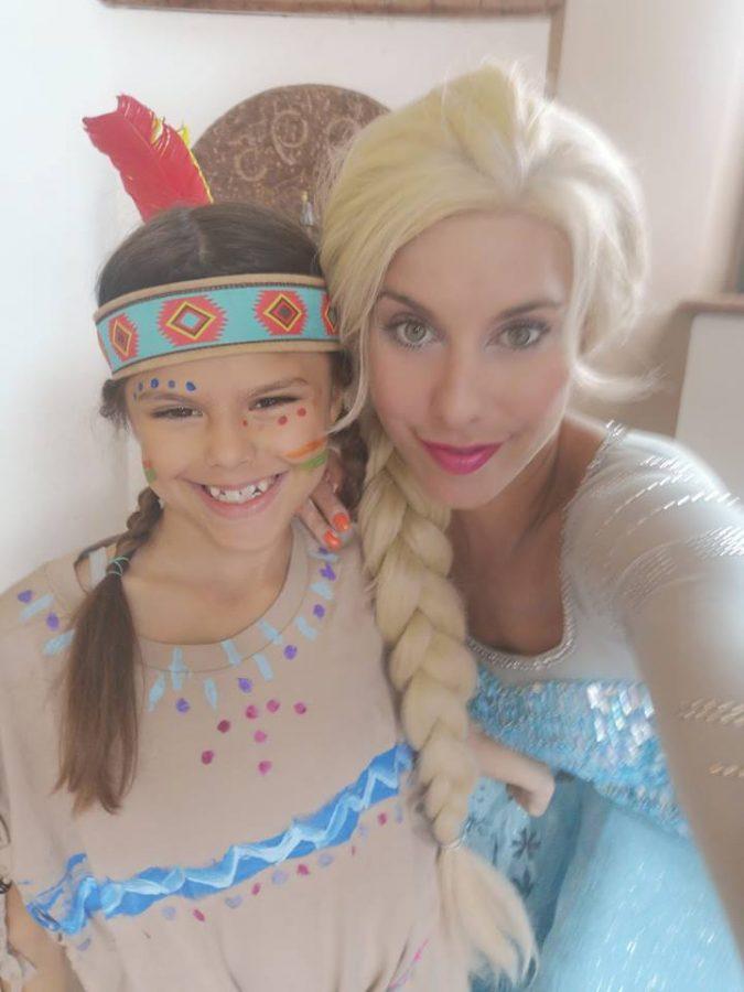 Die Elsa Eiskönigin mit einem Mädchen, das als Pocahontas verkleidet ist.